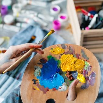Инструменты, необходимые художнику. крупным планом женские руки, держа деревянную палитру и кисть над размытыми трубками с краской.