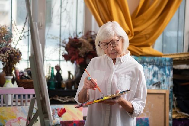 思いやりのあるアーティスト。彼女の新しい絵を描いている間思慮深く感じている眼鏡をかけている引退した芸術家
