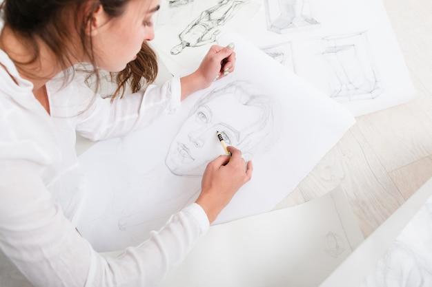 床に人間の鉛筆の肖像画を仕上げるアーティスト