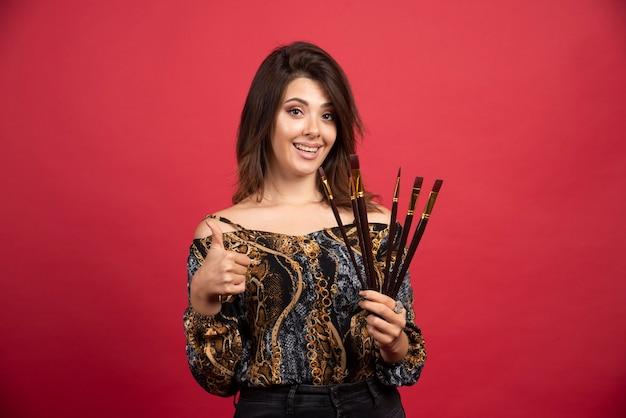 Ragazza artista che dimostra il suo set di pennelli nuovi di marca e sembra soddisfatta.