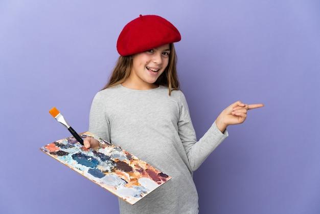 横に指を指し、製品を提示する孤立した背景上のアーティストの女の子