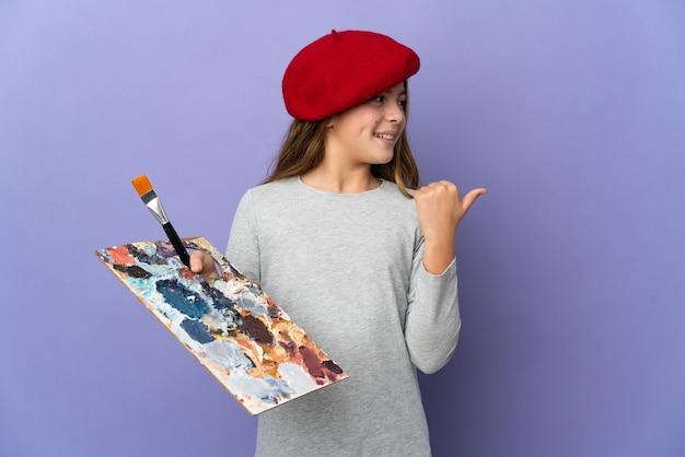 製品を提示する側を指している孤立した背景上のアーティストの女の子