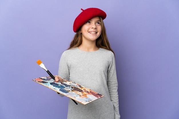 찾는 동안 아이디어를 생각하는 고립 된 벽 위에 아티스트 소녀