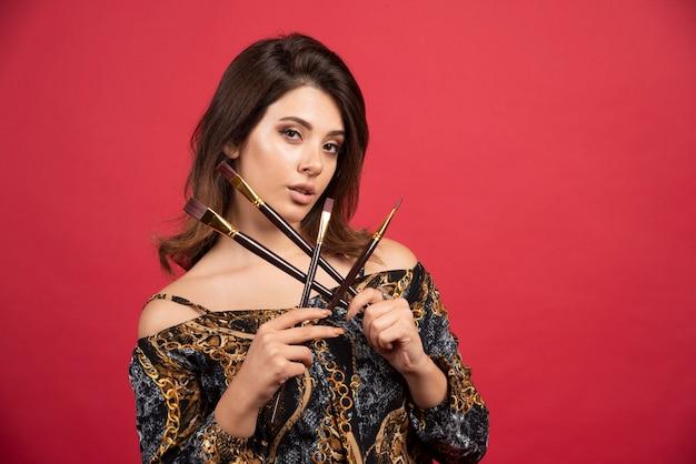 Ragazza artista in posa con il suo set di pennelli nuovi di marca in modo positivo.