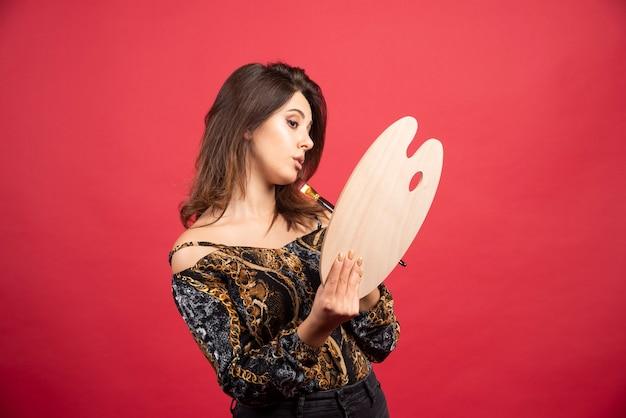 검토를 위해 큐레이터 또는 마스터에게 그녀의 팔레트를 보여주는 아티스트 소녀.