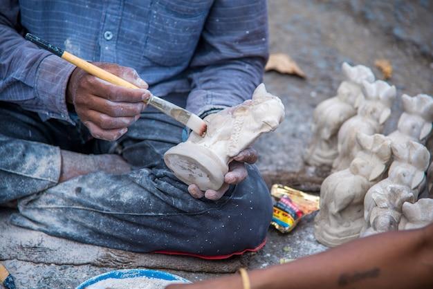 アーティストが保釈ブル ポーラ フェスティバルのワーク ショップで牛の像の仕上げを行います。