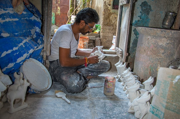 Artist gives finishing touches on statue of bull at an artist's workshop for bail (bull) pola festival.
