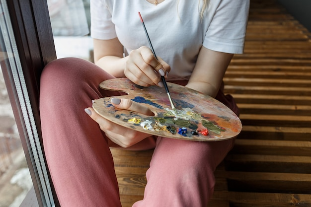 Artist hands with brush mixing colors on palette close up