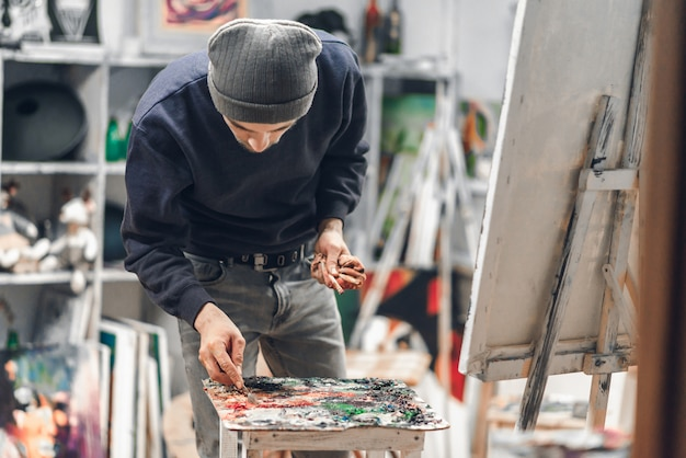 Artist holding a brush in his hand and picking up the paint with a palette knife