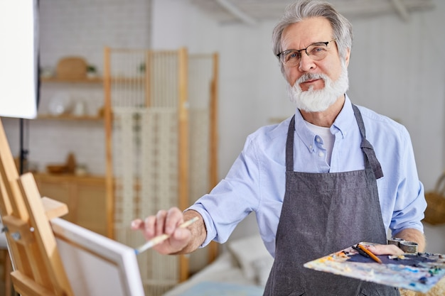 Artist holding creating masterpiece using paintbrush, stand near canvas, gray haired male in apron enjoy drawing