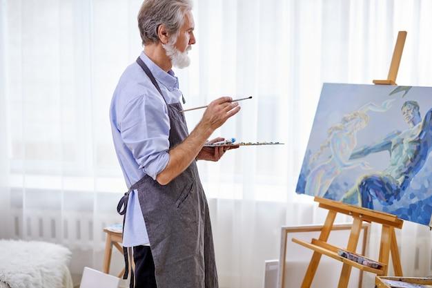 Художник держит шедевр с помощью кисти, стоит возле холста, седой мужчина в фартуке наслаждается рисованием