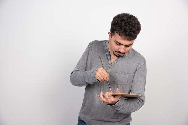 Художник держит свою деревянную палитру и кисть.