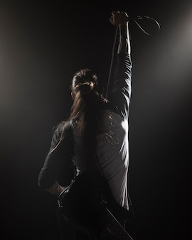 Artist holding a microphone on stage from the back