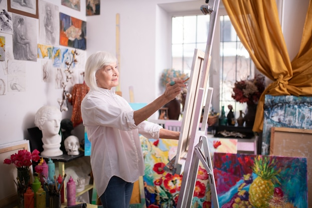 鉛筆を持つアーティスト。描画しながら鉛筆を保持している短いブロンドの髪を持つ美しい高齢者
