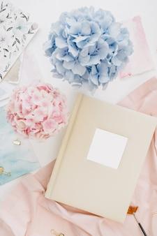가족 결혼식 사진 앨범, 파스텔 다채로운 수국 꽃다발, 복숭아 담요, 흰색 표면에 장식이있는 아티스트 홈 오피스 데스크