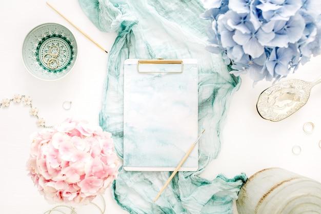 クリップボード、ターコイズブランケット、カラフルなパステルアジサイの花の花束、白い表面に女性のファッションアクセサリーとアーティストのホームオフィスデスクワークスペース。フラットレイ、上面図