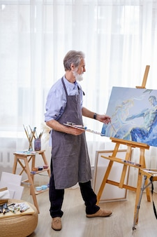 Artist immersed in the creation of art, painting canvas on easel. craftsman in apron enjoy painting, creating masterpiece