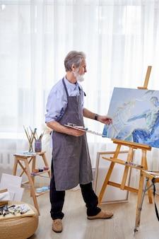 예술가는 이젤에 캔버스를 그리는 예술 창작에 몰두했습니다. 앞치마 장인이 그림을 즐기고 걸작을 만든다