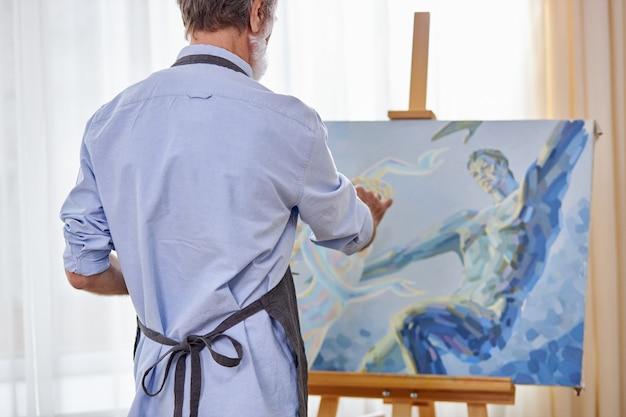 작업 중 앞치마를 입은 예술가, 파란색 그림으로 캔버스 반대편에 서십시오.