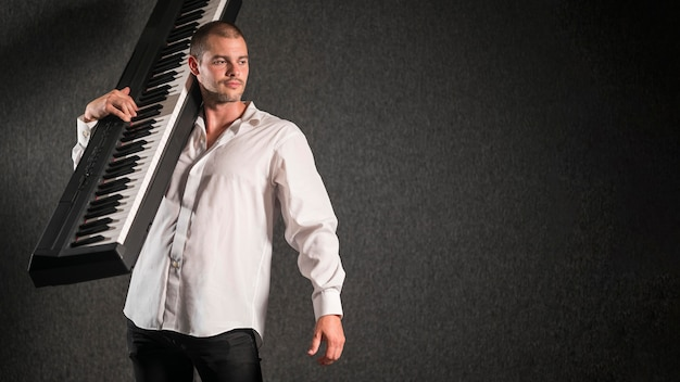 Художник в белой рубашке держит клавиатуру с копией пространства