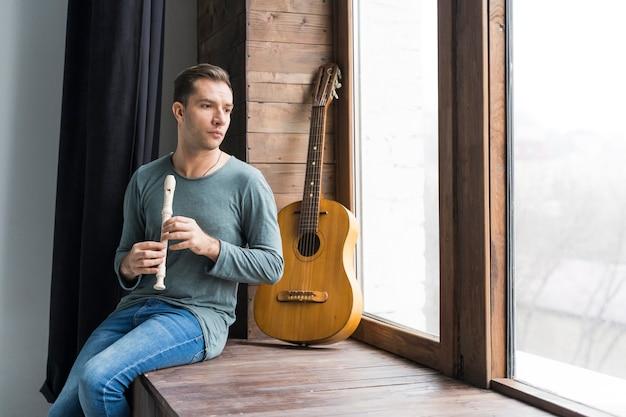 Артист в помещении играет на флейте и смотрит в окна