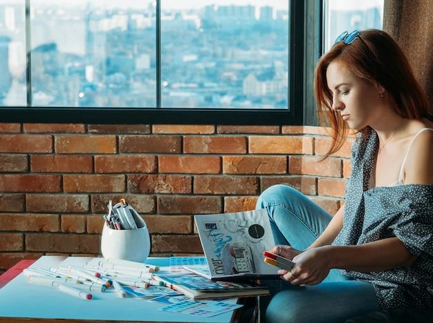 アーティストのインスピレーション。濃度。赤毛の女性画家は、パレットとフェルトペンでスケッチブックをめくります。