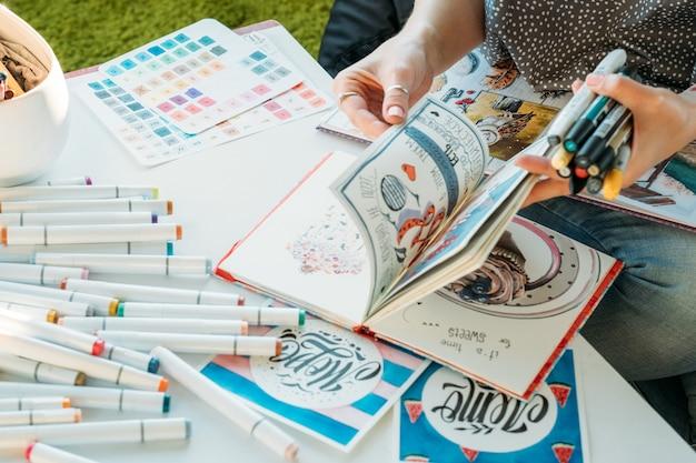 アーティストのインスピレーション。描画用品。パレットとフェルトペンでスケッチブックを弾く女性画家。