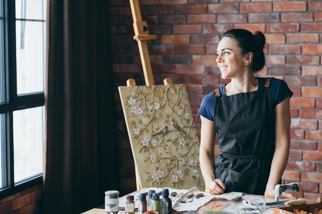アーティストのインスピレーション。夢のような熟考。窓を見ている笑顔の女性画家。イーゼルのキャンバス。職場での画材。
