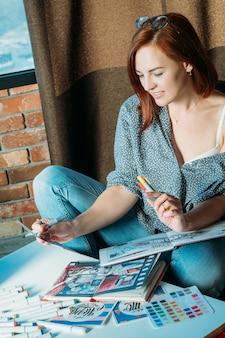 アーティストのインスピレーション。職場。スケッチブックや物資が周りにあるパレットを見ている思慮深い赤毛の女性画家。
