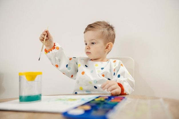 Artist is born. an adorable male toddler dressed in colorful dots sits at a table and draws with a brush and watercolors on paper. baby boy is focused on drawing. mental development of the child