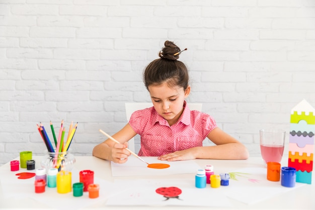 Artist kid painting on white paper over the desk against white brick wall