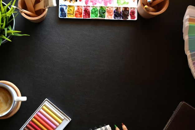 Artist leather desk top with creative supplies and copy space.