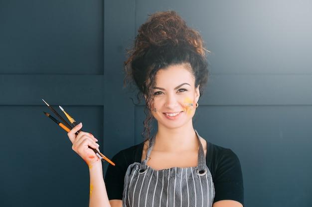 アーティストのライフスタイル。絵筆のセットを保持している女性の肖像画。顔や手がペンキで汚れている。