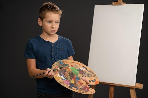 페인트 팔레트를 들고 슬픈 찾고 파란색 티셔츠에 아티스트 어린 소년
