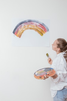 Artist looking at picture of rainbow in studio