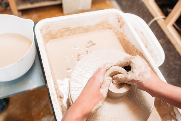 예술가는 물레에 도자기 바닥을 만듭니다.
