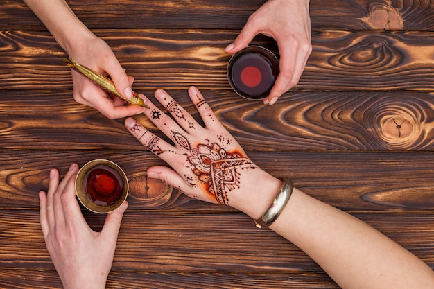 Artist making mehndi on womans hand and drinking tea