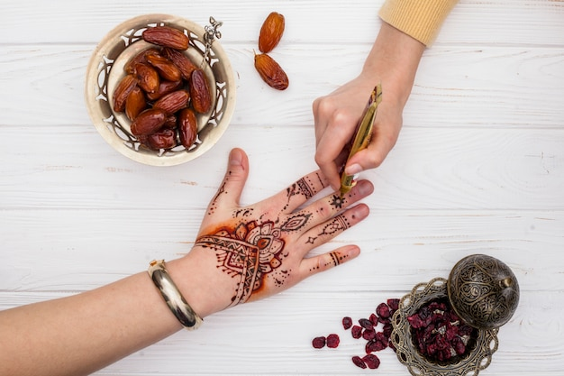 Artist making mehndi on womans hand near dates fruit