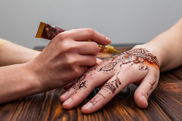 Artist making mehndi on womans hand on table