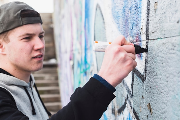 Художник, очерчивающий граффити на стене