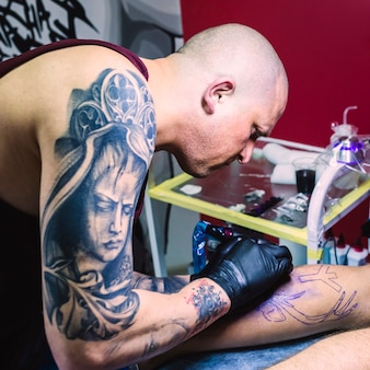 Artist making tattoo in colorful studio