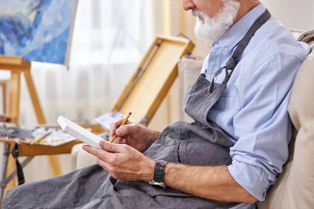 Artist male is drawing on small canvas with pencil, making sketch, sitting on sofa in apron
