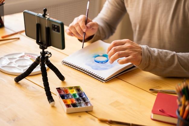 페인트 브러시 수채화 그림을 들고 스튜디오에서 학생들을 위해 온라인 미술 수업을 만드는 아티스트 남성