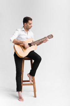 Художник человек в студии играет на классической гитаре