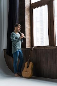 屋内でフルートを演奏するアーティスト男