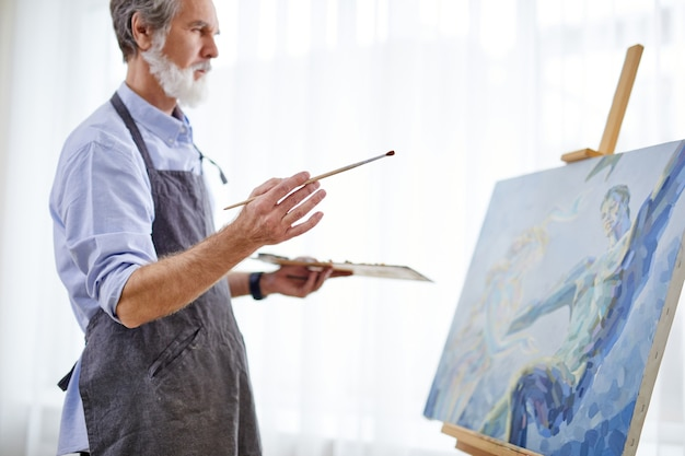 Artist man is drawing on easel canvas, senior gray haired man in apron enjoy the process of painting, in light room. side view
