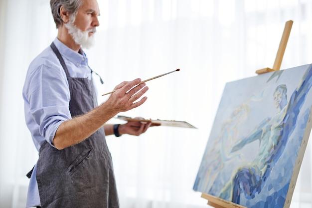 예술가 남자가 이젤 캔버스에 그림을 그리고 있으며, 앞치마를 입은 수석 회색 머리 남자는 밝은 방에서 그림을 그리는 과정을 즐깁니다. 측면보기