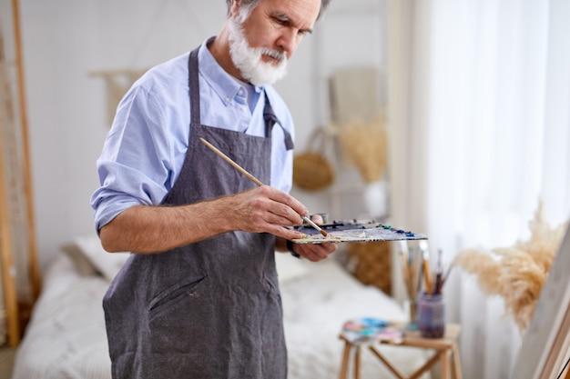 예술가 남자가 이젤 캔버스에 그림을 그리고 있으며, 앞치마를 입은 수석 회색 머리 남자는 밝은 방에서 그림을 그리는 과정을 즐깁니다.