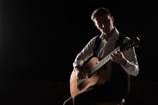 Артист мужчина на сцене играет на классической гитаре копией пространства