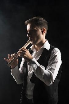 Артист мужчина на сцене играет на флейте